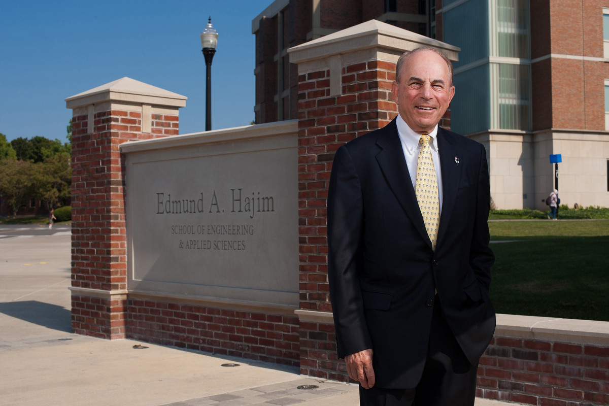 Ed Hajim standing in front of the sign bearing his name near the Hajim quad