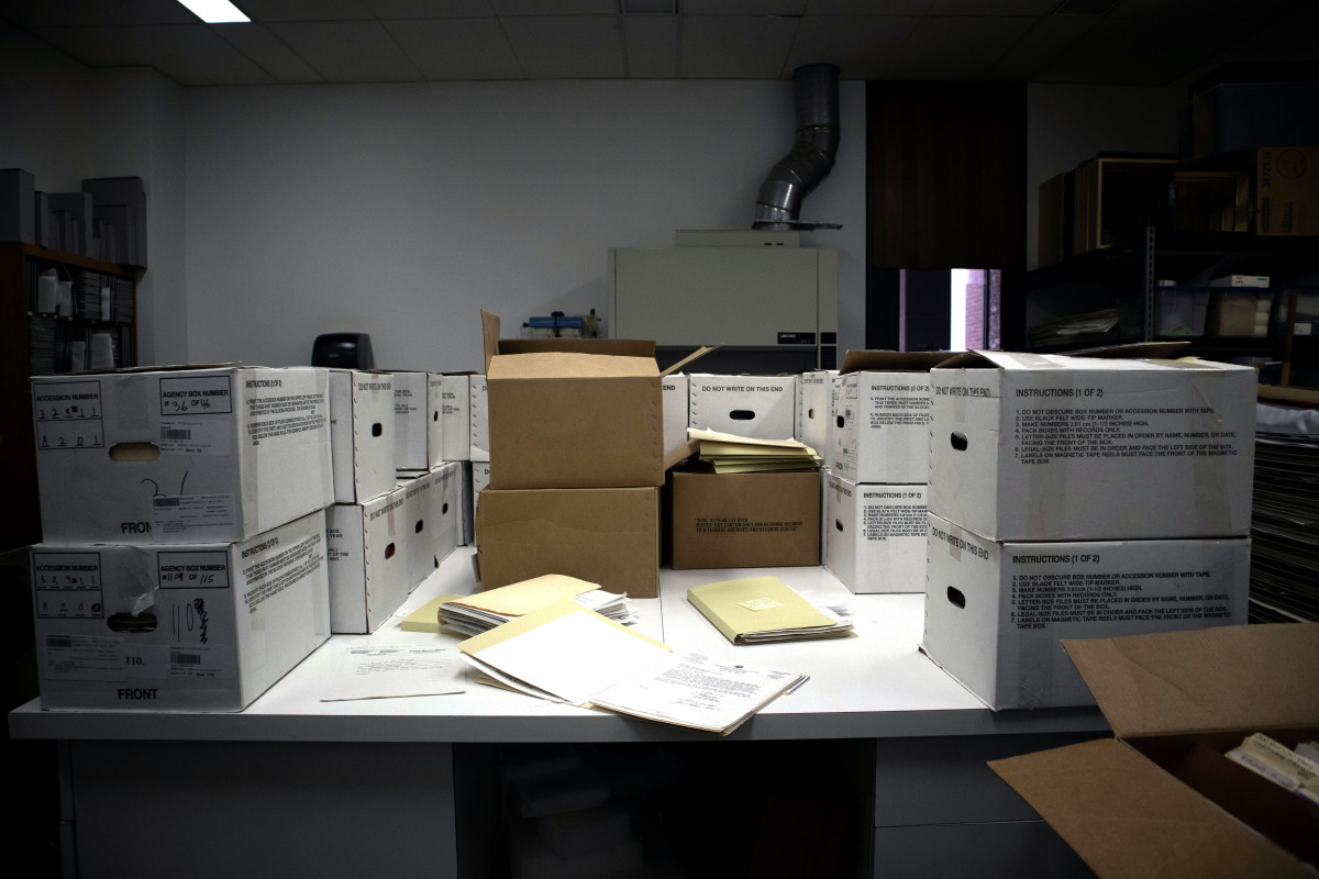 A table covered in banker's boxes, folders, and papers