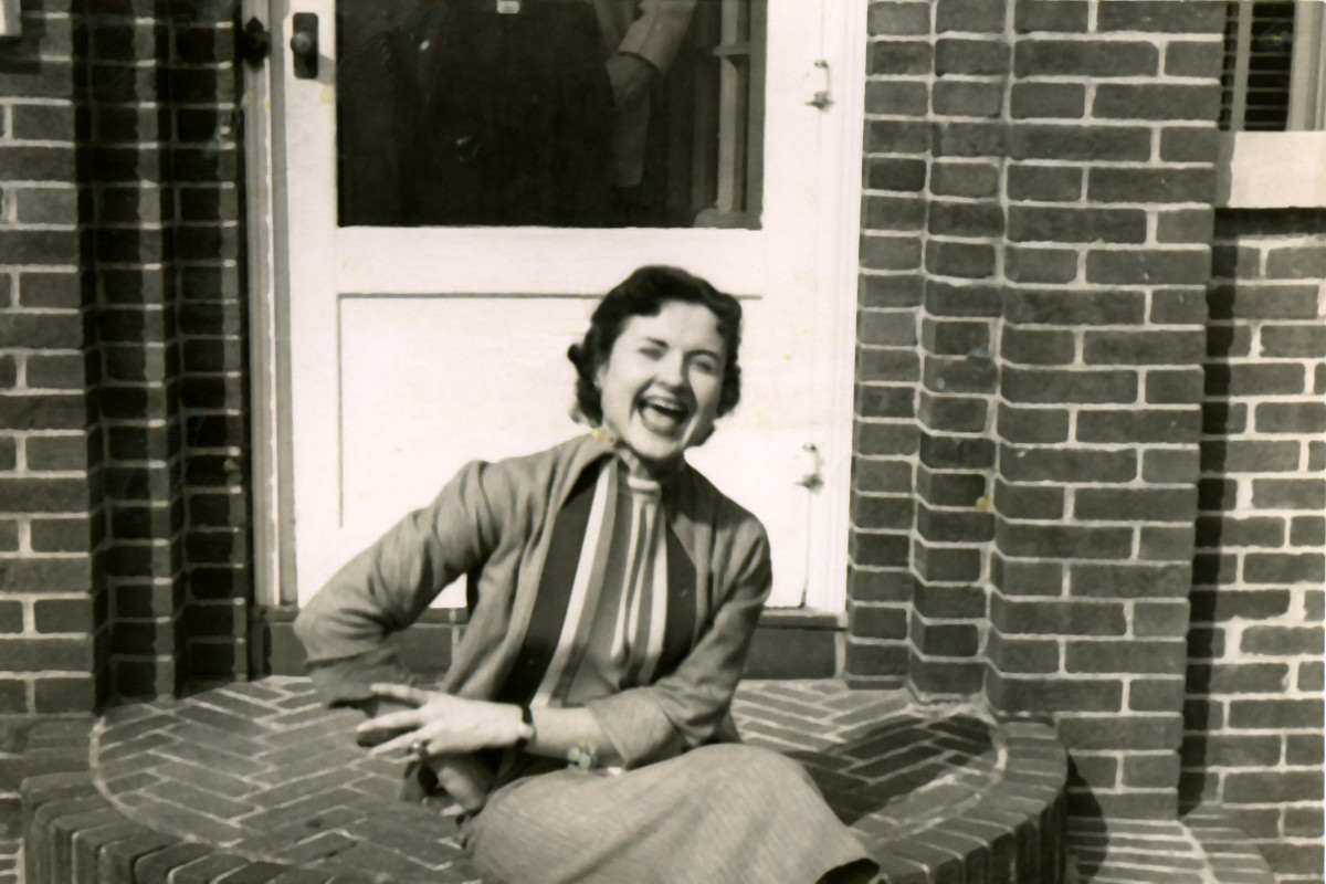 Louise Slaughter as a young woman, sitting and laughing on the stoop of a home believed to be hers in Fairport, NY