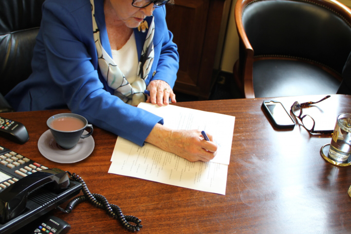 Congresswoman Louise Slaughter at a desk writing on a document with a cup of tea next to her