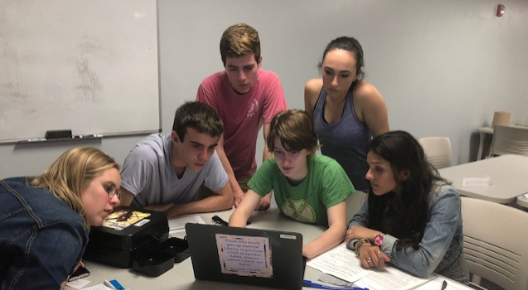 Students gathered around a laptop on a table
