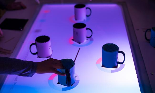 Coffee mugs on a glass table in Wegmans Hall are transformed into an AR classroom exercise that simulates a sprawling, real-life chemical plant.